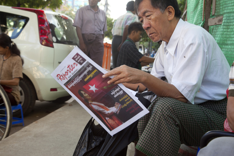 A man reads a newspaper covered with Myanmar opposition leader Aung San Suu Kyi at a roadside  stand Wednesday, Nov. 11, 2015, in Yangon, Myanmar. (AP Photo/Khin Maung Win)