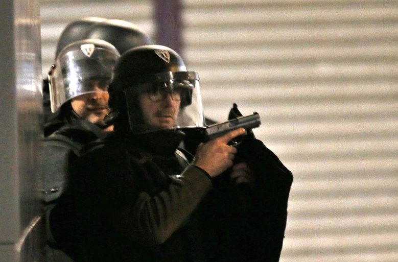 Armed police officers take up positions in Saint Denis, a northern suburb ofParis, Wednesday, Nov. 18, 2015. Authorities in the Paris suburb of Saint Denis are telling residents to stay inside during a large police operation near France's national stadium that two officials say is linked to last week's deadly attacks. (AP Photo/Francois Mori)