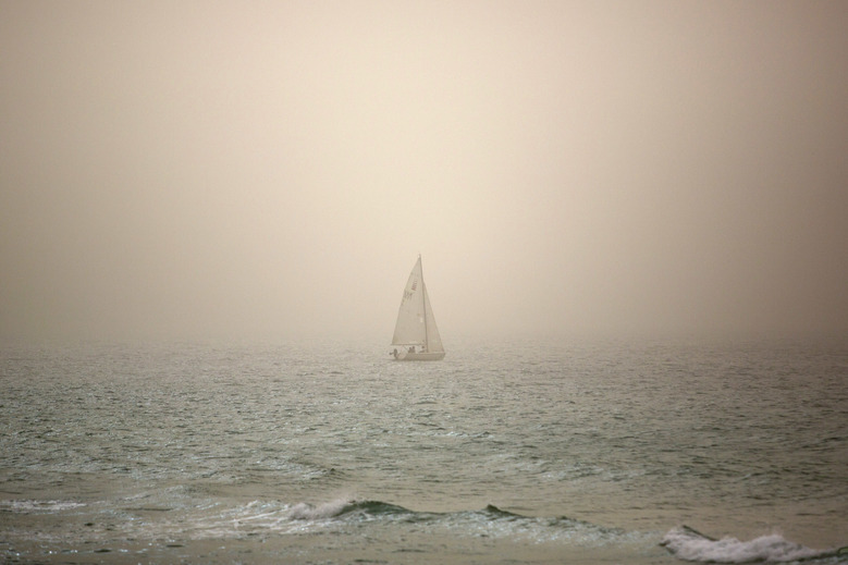 A boat makes its way through a sandstorm in the Mediterranean Sea, in Tel Aviv, Israel, Wednesday, Nov. 4, 2015. A thick sandstorm cloaked the Middle East on Wednesday, clouding skies across the region. In Israel, travel was disrupted for thousands of people when domestic flights to the resort town of Eilat were canceled because of the weather, as the haze shrouded parts of Israel.(AP Photo/Sebastian Scheiner)