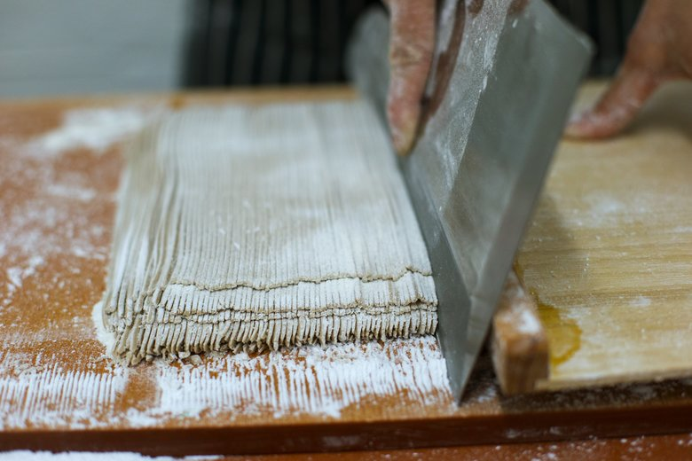 Chef Mutsuko Soma uses a special knife to cut freshly made buckwheat noodles. (John Lok/The Seattle Times)