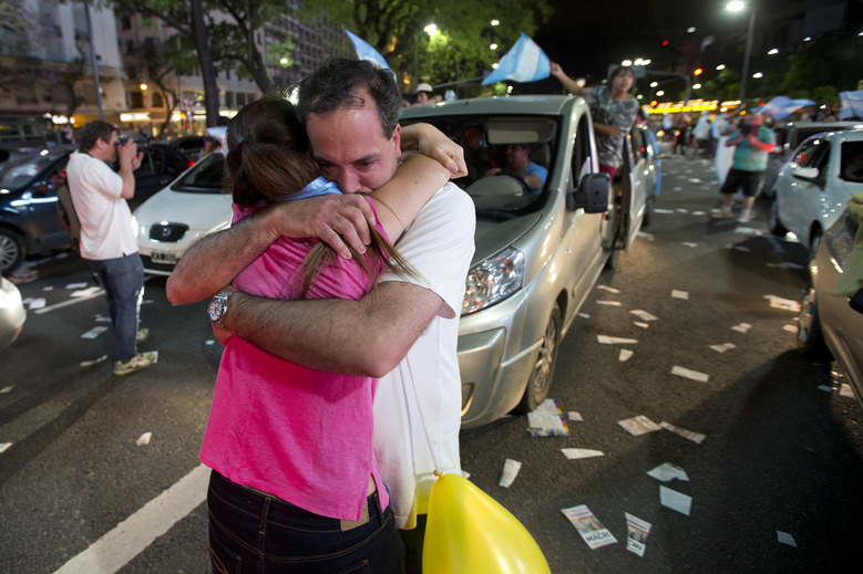 Supporters of presidential candidate Mauricio Macri hug as they celebrate in Buenos Aires,  Sunday, Nov. 22, 2015.  Macri won Argentina's historic runoff election against ruling party candidate Daniel Scioli, putting an end to the era of  President Cristina Fernandez, who along with her late husband dominated Argentine politics for 12 years.(AP Photo/Victor R. Caivano)