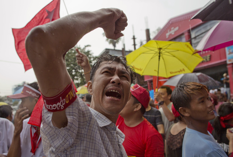 Braving rain, a supporter of Myanmar's National League for Democracy party shouts slogans outside the NLD headquarters in Yangon, Myanmar, Monday, Nov. 9, 2015. Opposition leader Aung San Suu Kyi's NLD party was confident Monday that it was headed for a landslide victory in Myanmar's historic elections, as the democracy icon urged supporters not to provoke losing rivals who mostly represent the former junta that ruled this Southeast Asian nation for a half-century. (AP Photo/Gemunu Amarasinghe)