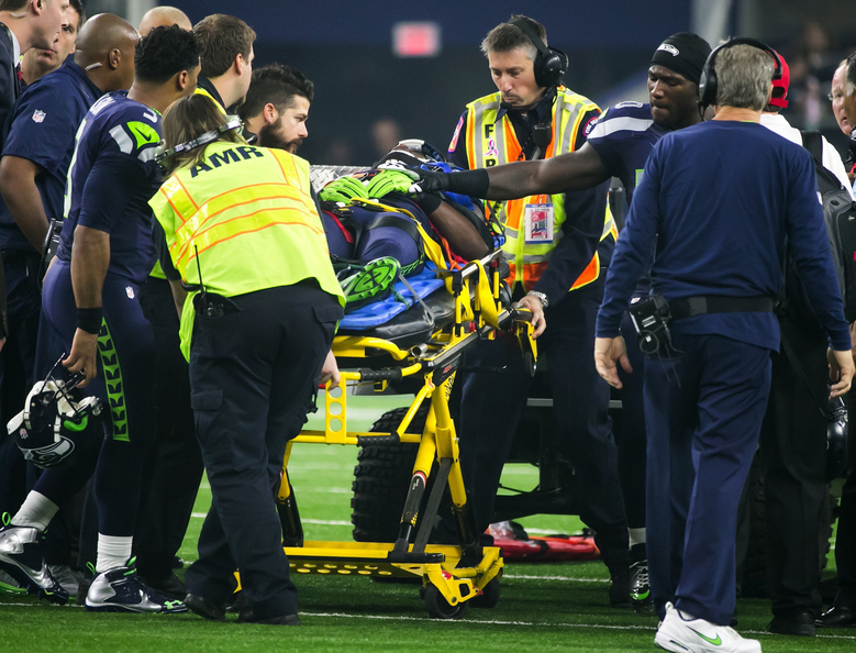 Seahawks fullback Derrick Coleman puts his hand on Ricardo Lockette's as Lockette is taken to an ambulance in after a hard hit in the second quarter. (Bettina Hansen/The Seattle Times)