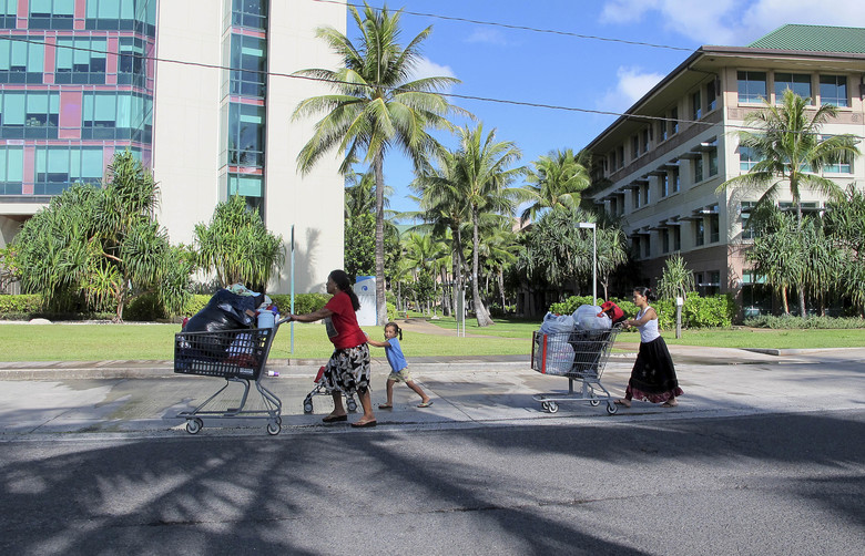 In this Oct. 7, 2015 photo, Kionina Kaneso, left, pushes carts of laundry followed by her granddaughter, Keioleen Helly, center, and daughter, Kifency Kinny, past the University of Hawaii John A. Burns School of Medicine near a tent in a homeless encampment in which they lived in Honolulu. Homelessness in Hawaii has grown in recent years, leaving the state with 487 homeless per 100,000 people, the nation's highest rate per capita, ahead of New York and Nevada, according to federal statistics. (AP Photo/Cathy Bussewitz)