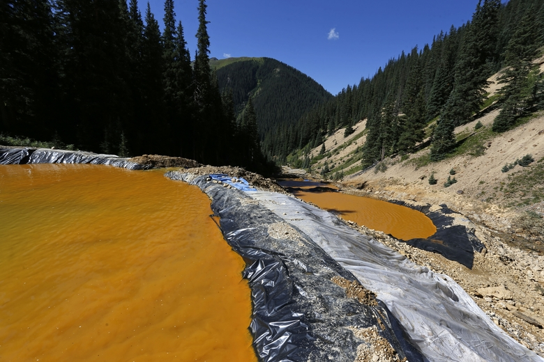 In this Aug. 14, 2015 photo, water flows through a series of sediment retention ponds built to reduce heavy metal and chemical contaminants from the Gold King Mine wastewater accident, in the spillway about 1/4 mile downstream from the mine, outside Silverton, Colo.  Colorado officials are disputing a key claim by federal agencies about a massive spill of toxic wastewater from an inactive mine. A report by the federal Bureau of Reclamation, said two state mining experts signed off on an Environmental Protection Agency cleanup project that led to the Aug. 5 spill at the Gold King Mine in southwest Colorado. (AP Photo/Brennan Linsley)