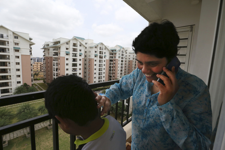 Many Indians return to be near family. Vasantha Gullapalli, on her balcony with son Abhiram, calls her sister Anita Chitturi Jagdeesh who lives across this gated complex in Hyderabad. Gullapalli returned with her husband, Sekhar Boddu, who works for Amazon.  (Alan Berner / The Seattle Times)
