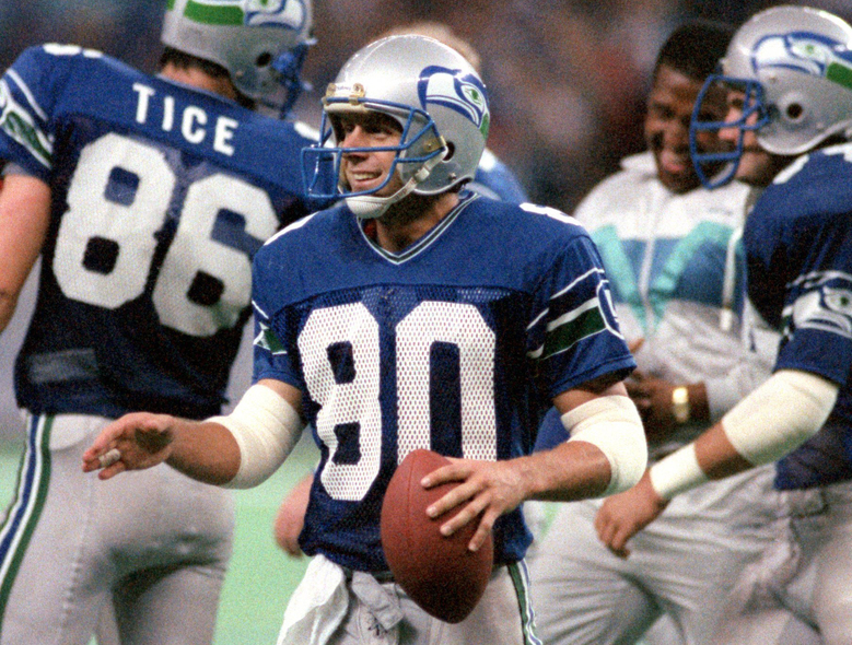 In 1986, Steve Largent has the ball he caught in an NFL-record 128th consecutive game and a big smile as he reaches out to shake one of many hands thrust toward him.  (Betty Udesen/The Seattle Times)