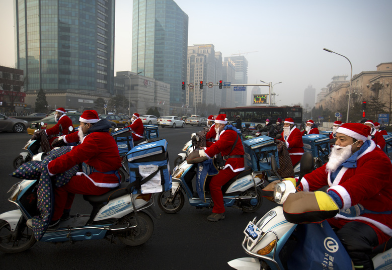 Food delivery drivers dressed in Santa Claus suits cross an intersection on a day with strong air pollution in Beijing, Wednesday, Dec. 23, 2015. Although not an official holiday in China, Christmas is marked as a shopping and commercial event in China's capital. (AP Photo/Mark Schiefelbein)