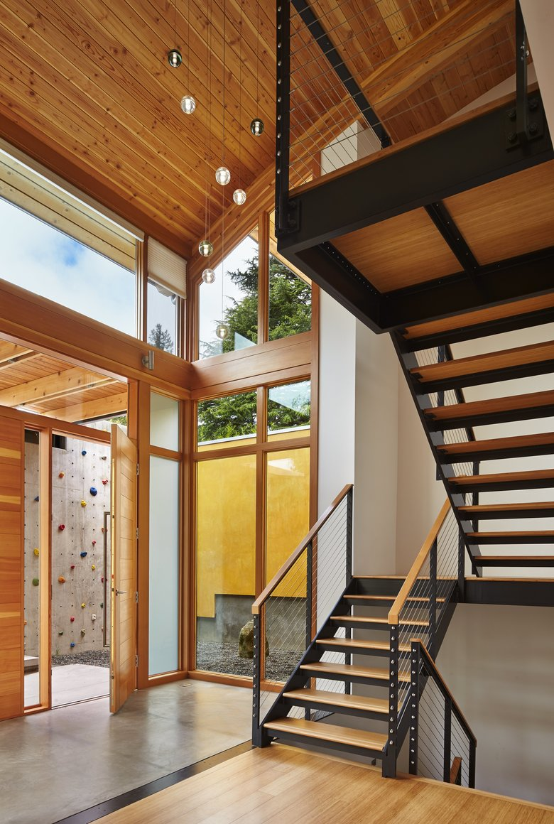 The arched eyebrow of a roofline creates a sweeping and grand two-story entry. The climbing wall just outside in the courtyard is a spot for energetic boys to burn off energy. (Benjamin Benschneider/The Seattle Times)