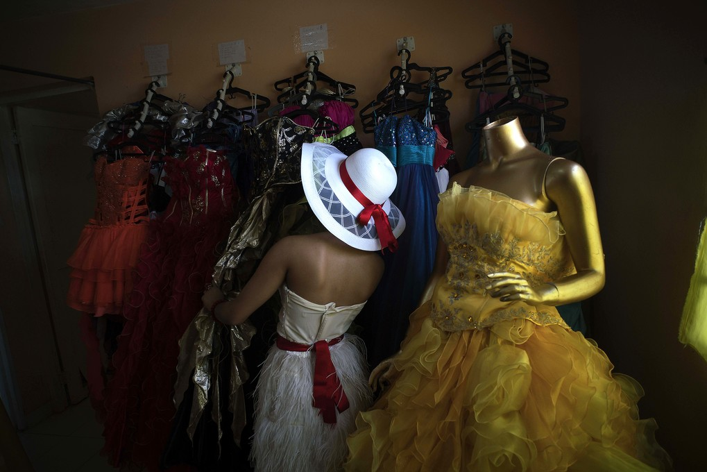 """In this Dec. 18, 2015 photo, Daniela Santos Torres, 14, chooses a dress for her quinceanera party at Estudio Mayer, the company her family hired to take her portraits and organize her birthday party in Havana, Cuba. Daniela left Cuba when she was 3, returning in December for her quinceanera photos and party. She now lives in Glendale, Arizona, where her father runs a home remodeling business. She said returning to Cuba for her celebration was """"a dream,"""" allowing her to include her extended family and friends on the island. (AP Photo/Ramon Espinosa)"""