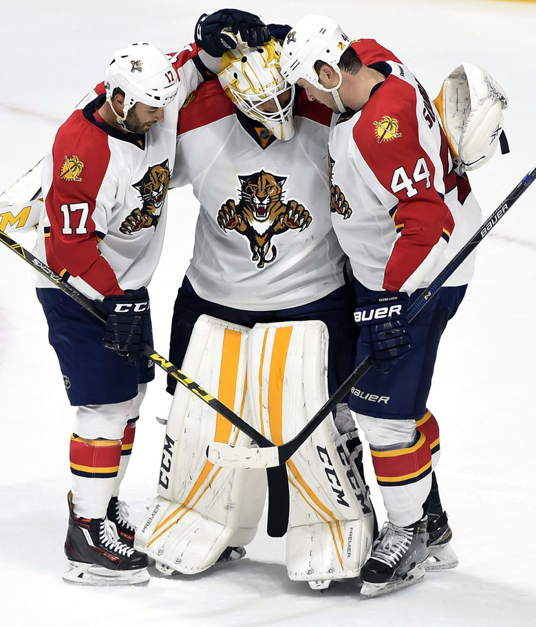 Florida Panthers center Derek MacKenzie (17) and defenseman Erik Gudbranson (44) congratulate goalie Roberto Luongo (1) after the Panthers defeated the Nashville Predators 2-1 in an NHL hockey game Thursday, Dec. 3, 2015, in Nashville, Tenn.  (AP Photo/Mark Zaleski)