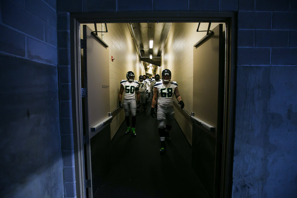 Seahawks linebacker K.J. Wright and offensive lineman Justin Britt come down the hallway with the team to take the field for pregame warmups. (Bettina Hansen / The Seattle Times)