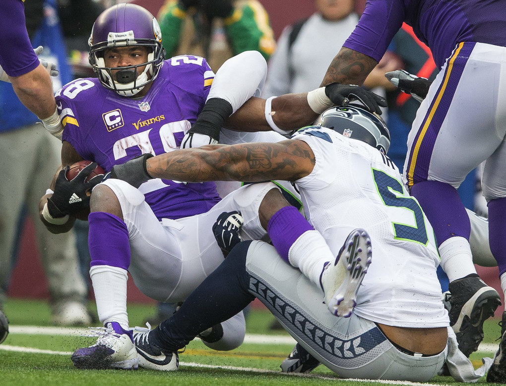 Bruce Irvin drops Minnesota running back Adrian Peterson for a 1-yard loss in the third quarter. (Dean Rutz / The Seattle Times)