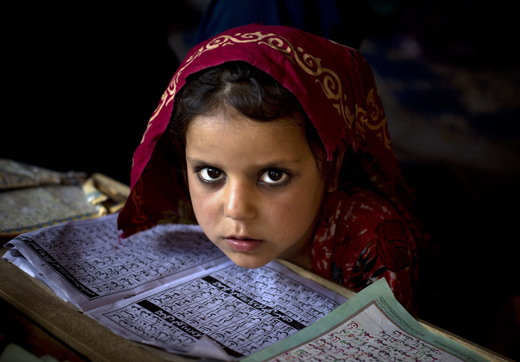 In this Monday, April 26, 2015 photo, an internally displaced Pakistani girl from a tribal area attends her daily lesson at a madrassa, a school for the study of Islam, on the outskirts of Islamabad, Pakistan. (AP Photo/B.K. Bangash, File)