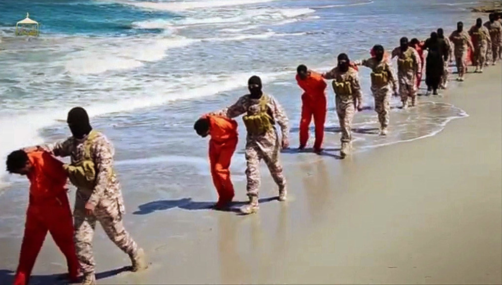 In this undated image made from a video released by Islamic State militants on April 19, 2015, which has been verified and is consistent with other AP reporting, members of an IS affiliate walk captured Ethiopian Christians along a beach in Libya. The video purportedly shows two groups of captives: one held by an IS affiliate in eastern Libya and the other by an affiliate in the south. A masked militant delivers a long statement before the video switches between footage that purportedly shows the captives in the south being shot dead and the captives in the east being beheaded on a beach. (Militant video via AP, File)