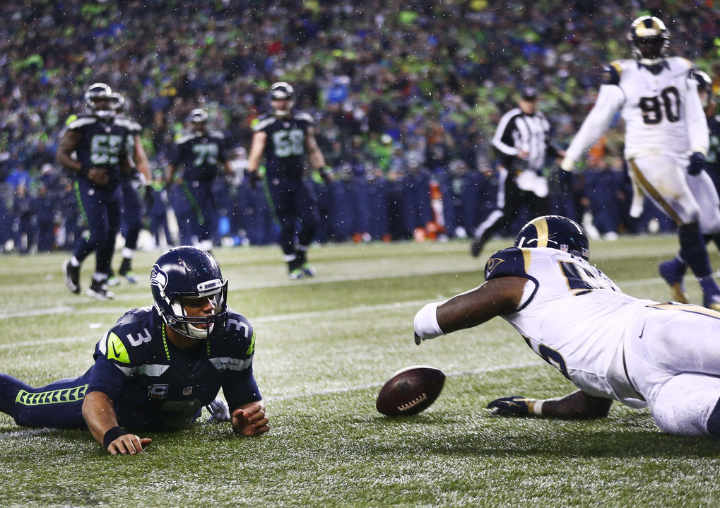 Seahawks quarterback Russell Wilson, who thought he was down, watches as Rams linebacker Akeem Ayers recovers the ball to give the Rams possession late in the fourth quarter. (Lindsey Wasson / The Seattle Times)