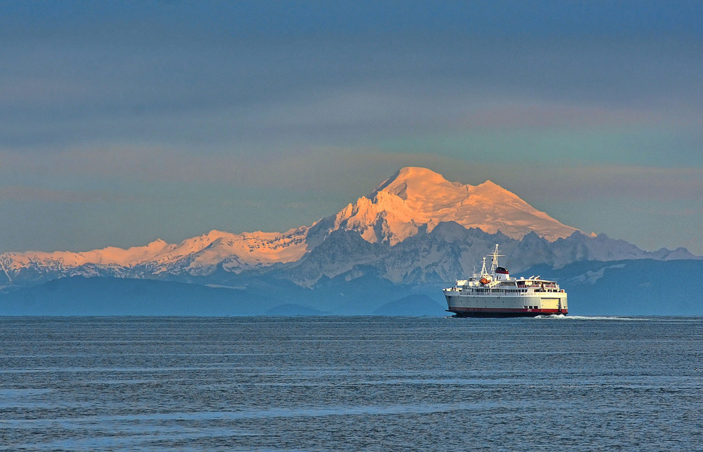 "Photographer: Jay Cline, Port Angeles.  Photo taken: Dec. 11, Port Angeles waterfront.  Photographer's description: ""The Black Ball ferry, the Coho, leaving Port Angeles, with Mount Baker in the background. Taken with a Nikon D7100, Nikkor 80-200 lens, at 200mm, 1/160th, f/11, ISO 100.""  Katie's critique: ""What a breathtaking photo. I enjoy the simplicity and cleanness of it, with the huge ferry highlighted against the gigantic mountain. The light is stunning and nicely hits the ferry and Mount Baker, allowing them to stand out against the beautiful pastels of the sky."""