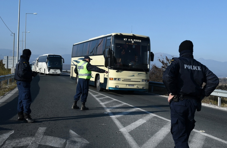 Police officers give directions to the bus drivers as they leave with stranded migrants from the Greek-Macedonian border to Athens after a police operation near the northern Greek village of Idomeni, Wednesday, Dec. 9, 2015. More than 200 riot police have been deployed to the border area at Idomeni following the standoff that has halted freight rail services from Greece to other European countries. (AP Photo/Giannis Papanikos)