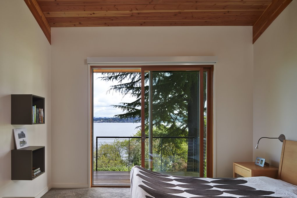 The master bedroom is a place restful and restorative, with its own deck into the trees, over the lake.  (Benjamin Benschneider/The Seattle Times)