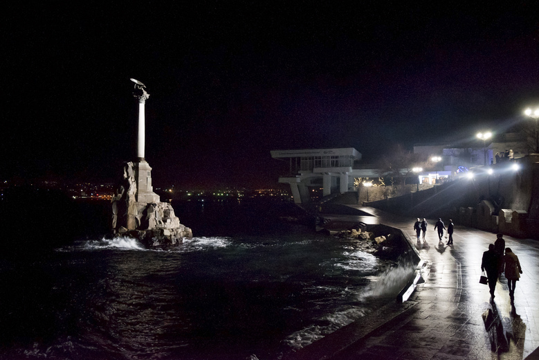 In this photo taken on Sunday, Dec.  27, 2015, with a city landmark, the Monument to the Scuttled Ships, at left, people walk along the Black Sea shore. The monument marks the scuttling of the Russians ships in 1854 to protect the harbor from Allied troops (United Kingdom, French and Italy's Piedmontese) which landed in the Crimea and besieged Sevastopol during the Crimean War. As New Year's Eve approaches, the central square of Crimea's largest city is festooned with lighted holiday decorations, including a soaring artificial tree that flashes and winks. But areas a few steps away are sunk in darkness, the streetlamps turned off because of an electricity shortage. (AP Photo/Alexander Polegenko)