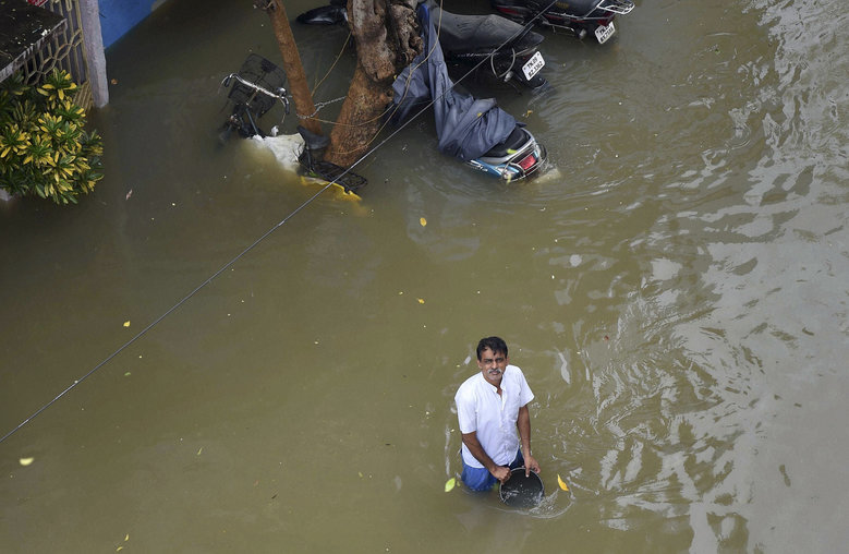 A man waits for food packets in floodwaters following heavy rains in Chennai, India, Thursday, Dec. 3, 2015. The heaviest rainfall in more than 100 years has devastated swathes of the southern Indian state of Tamil Nadu, with thousands forced to leave their submerged homes, schools and offices, and a regional airport remained shut for a second day Thursday. (Atul Yadav/ Press Trust of India via AP)