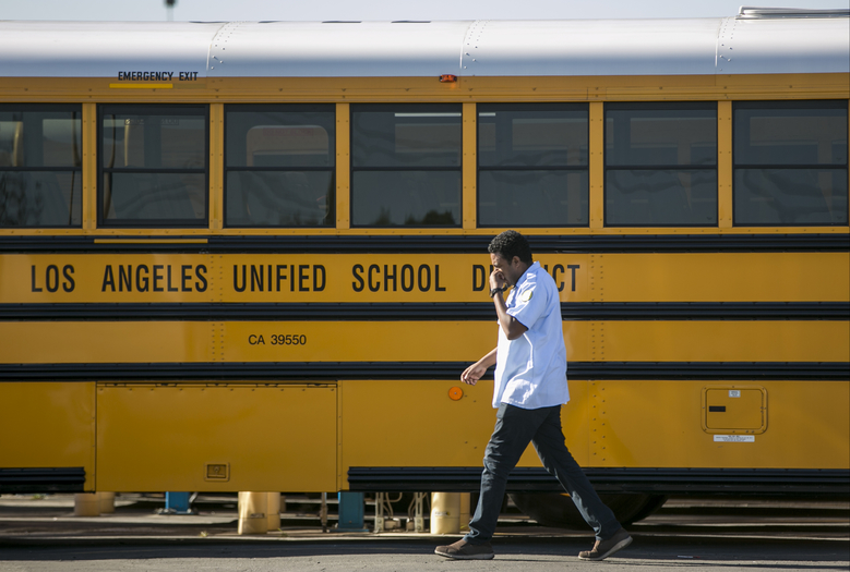 A Los Angeles Unified School District bus driver walks past parked vehicles at a bus garage in Gardena, Calif., on Tuesday, Dec. 15, 2015. The nation's two biggest school systems, New York City and Los Angeles, received threats of a large-scale attack Tuesday, and L.A. reacted by shutting down the entire district. New York dismissed the warning as an amateurish hoax and held class as usual. In LA, the threat came in the form of an email to a school board member that raised fears of another attack like the recent deadly shooting in nearby San Bernardino. (AP Photo/Damian Dovarganes)