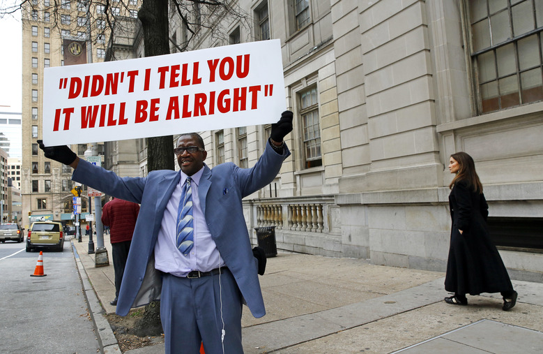 """Ronnie """"Church"""" Brown displays a sign to passing traffic outside of a courthouse during jury deliberations for William Porter, one of six Baltimore city police officers charged in connection to the death of Freddie Gray, Wednesday, Dec. 16, 2015, in Baltimore. (AP Photo/Patrick Semansky)"""