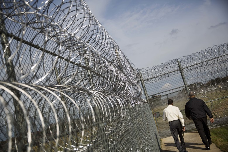 Deputy Warden of Security Keith Eutsey, left, and Warden Bruce Chatman walk to the execution chamber along rows of barbed wire at the Georgia Diagnostic and Classification Prison, Tuesday, Dec. 1, 2015, in Jackson, Ga. Death row inmates don't have far to go when their appeals run out. The chamber where lethal injections take place, a small room with a gurney, separated by a large pane of glass from the observation area, is on the grounds. (AP Photo/David Goldman)