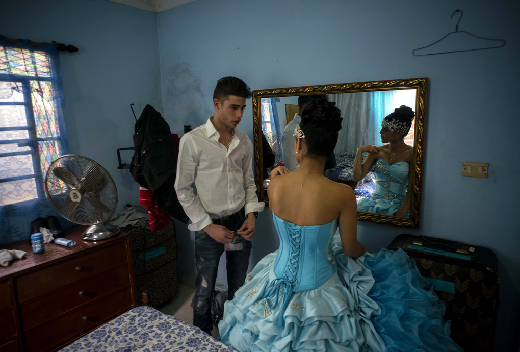 """In this Dec. 20, 2015 photo, Daniela Santos Torres, 15, speaks with her boyfriend Erick before her quinceanera party in the town of Punta Brava near Havana, Cuba. Daniela left Cuba when she was 3, returning in December for her quinceanera photos and party. She now lives in Glendale, Arizona, where her father runs a home remodeling business. She said returning to Cuba for her celebration was """"a dream,"""" allowing her to include her extended family and friends on the island. (AP Photo/Ramon Espinosa)"""