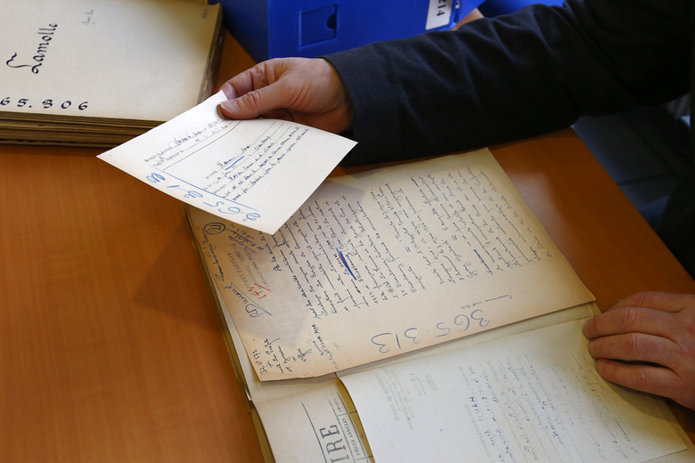 Gilles Morin, a French historian holds a file of of the collaborationist regime led by Philippe Petain from 1940 to 1944, in the 'reading room' of the Paris Police Prefecture Archives department, in Paris, France, Tuesday, Dec. 29, 2015. France is opening police and legal archives from the collaborationist Vichy regime, allowing free access to previously classified documents from World War II. (AP Photo/Francois Mori)