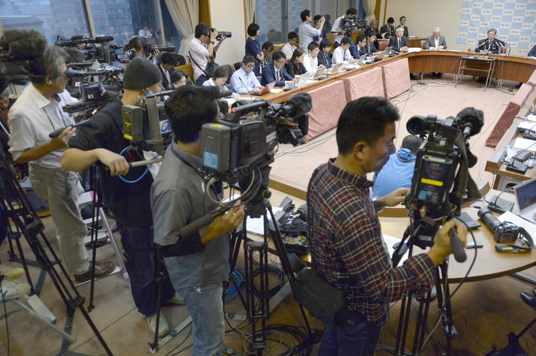 """TV cameramen film Okinawa Gov. Takeshi Onaga, top right, speaking at a news conference in Naha, Okinawa, after filing a lawsuit against the central government in a bid to stop the relocation of a U.S. air base on the southern Japanese island Friday, Dec. 25, 2015. We will do whatever it takes to stop the new Henoko base,"""" Onaga told reporters. """"Okinawa's argument is legitimate, and I believe that it will be certainly understood."""" (Munehide Someya/Kyodo News via AP) JAPAN OUT, CREDIT MANDATORY"""