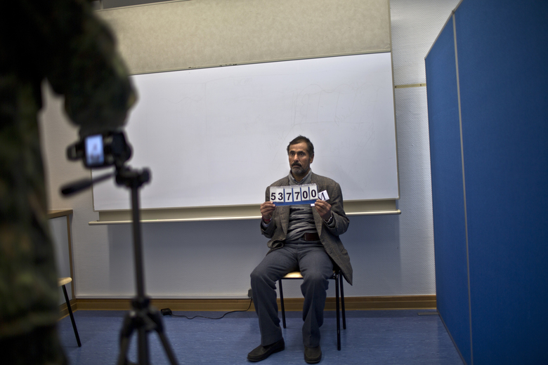 In this Wednesday, Dec. 9, 2015 photo, a German army officer takes a photo of Samir Qasu, 45, a Yazidi refugee from Sinjar, Iraq, as part of his asylum seeking process, at the Central Registration Centre in Patrick Henry Village in Heidelberg, Germany. (AP Photo/Muhammed Muheisen)