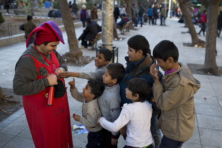 A volunteer dressed as a clown gives balloons to refugee children at Victoria square in Athens, on Wednesday, Dec. 23, 2015. The Geneva-based International Organization for Migrants says more than 1 million people have entered Europe as of Monday. Almost all came by sea, while 3,692 drowned in the attempt. At least 820,000 refugees and economic migrants have reached Greece's eastern islands this year. (AP Photo/Petros Giannakouris)