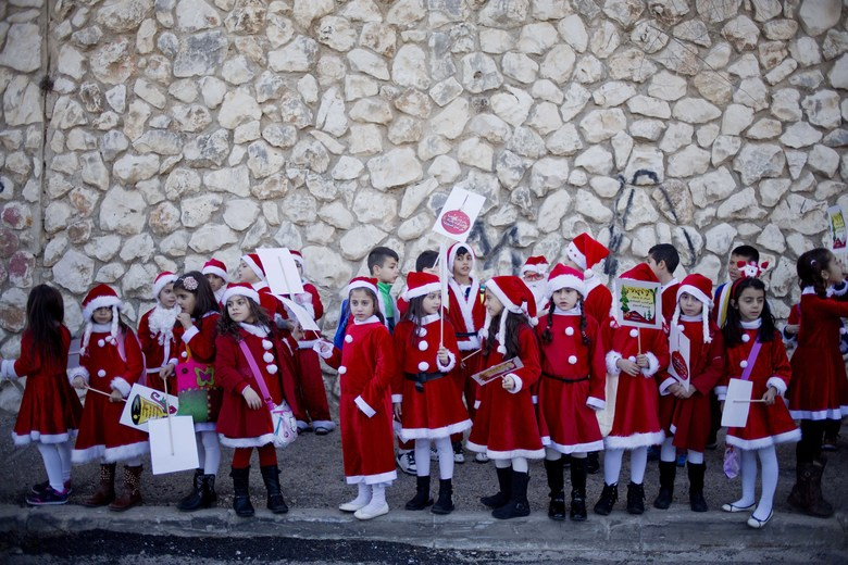 FILE – In this Thursday, Dec. 24, 2015 file photo, Israeli Arab Christians dressed up as Santa Claus wait for the start of the annual Christmas parade in in the northern Israeli city of Nazareth, Israel, on Christmas Eve. (AP Photo/Ariel Schalit, File)