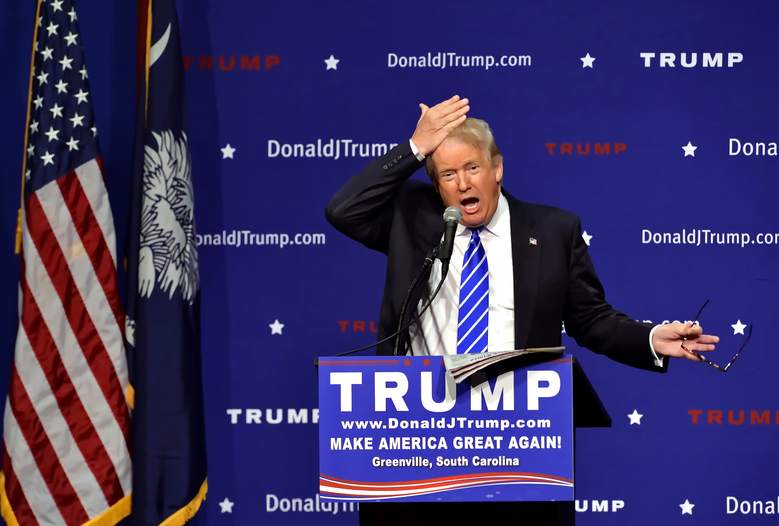 FILE – In this Thursday, Aug.  27, 2015 file photo, Republican presidential candidate Donald Trump pulls his hair back to show that it is not a toupee while speaking during a rally at the TD Convention Center in Greenville, S.C. (AP Photo/Richard Shiro)