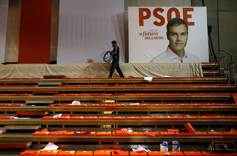 "A worker winds a cable next to a poster of Pedro Sanchez, leader of the Socialist party, after a closing campaign rally in Madrid, Spain, Friday, Dec. 18, 2015. The rise of two influential new parties to challenge the two traditional parties of government has injected tension and suspense into Sunday's ballot, where voters will give their verdict on promises to end high unemployment and corruption scandals in the European Union's fifth-largest economy. Poster reads in Spanish, ""Vote for a future for the majority"". (AP Photo/Francisco Seco)"