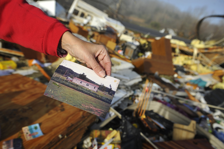 Diana Davis shows a photo she found in the rubble of her father-in-law's home after Wednesday's tornado in Lutts, Tenn., Thursday, Dec. 24, 2015. The photo shows what the house looked like before the tornado hit the area. (Larry McCormack/The Tennessean via AP) MANDATORY CREDIT
