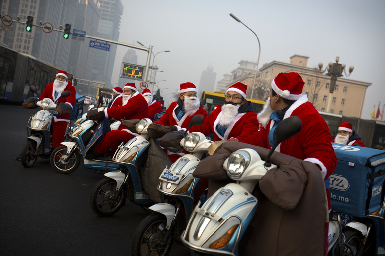 Food delivery drivers dressed in Santa Claus suits wait to cross the street at an intersection on a day with strong air pollution in Beijing, Wednesday, Dec. 23, 2015. Although not an official holiday in China, Christmas is marked as a shopping and commercial event in China's capital. (AP Photo/Mark Schiefelbein)