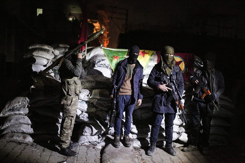 Militants of the Kurdistan Workers' Party, or PKK, stand at a barricade in Sirnak, Turkey, late Wednesday, Dec. 23, 2015. Security forces have killed 183 Kurdish rebels in a week in southeast Turkey, news agencies reported. The government imposed curfews in the mainly Kurdish towns of Cizre, Silopi, Nusaybin and Sur district of Diyarbakir as the security forces battle militants linked to the PKK who have moved their fight for autonomy to some towns and city neighborhoods in southeastern Turkey.(AP Photo/Cagdas Erdogan)