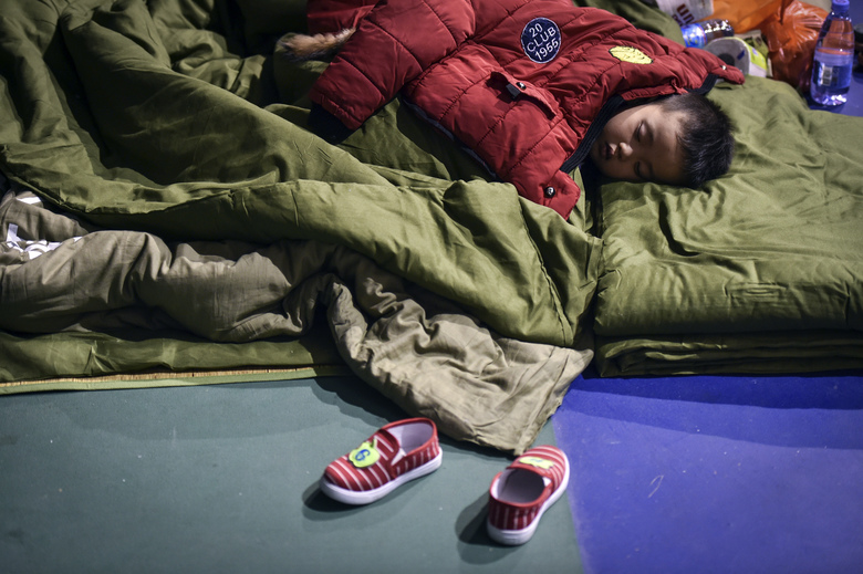 In this photo released by China's Xinhua News Agency, an evacuated boy rests at a makeshift shelter place located at a sports center in Shenzhen, south China's Guangdong Province Monday, Dec. 21, 2015. More than 50 people were missing Monday, a day after a massive landslide buried dozens of buildings when it swept through an industrial park in the southern Chinese city of Shenzhen. (Mao Siqian/Xinhua via AP) NO SALES
