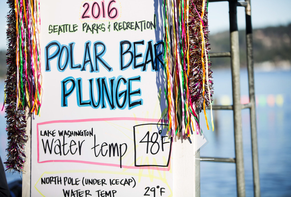 A festive sign shows the afternoon's water temperature compared to that of the North Pole for the 14th annual Polar Bear Plunge at Matthews Beach Park in Seattle on New Year's Day, Friday, Jan. 1, 2016. Hundreds of participants took the plunge into an estimated 48-degree Lake Washington, while air temperatures hovered at about 40 degrees during the noontime event.   (Lindsey Wasson / The Seattle Times)