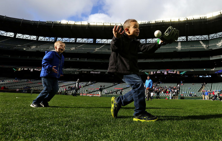 Brayden Cleveland, 6, snags a ball on the heel of his glove as Jordan Trout, 5, waits for one to be thrown to him in the outfield at Safeco Field during FanFest.  (Alan Berner / The Seattle Times)