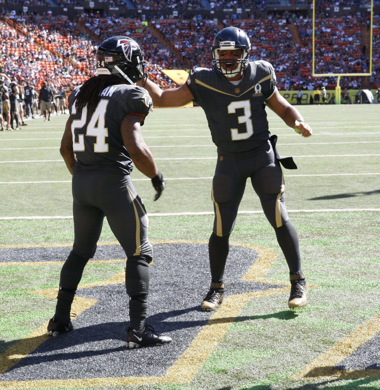 Atlanta Falcons running back Devonta Freeman (24) and Seattle Seahawks quarterback Russell Wilson (3) T of Team Irvin  celebrate after Freeman made a touchdown during the first quarter of the NFL Pro Bowl football game, Sunday, Jan. 31, 2016, in Honolulu. (AP Photo/Marco Garcia)