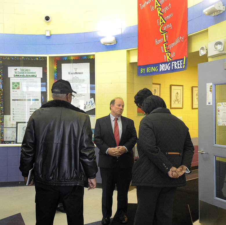 Detroit Mayor Mike Duggan, center, talks with school officials officials about the conditions at Fisher Magnet Lower Academy Tuesday, Jan. 12, 2016, in Detroit. The visits occurred while two dozen schools were closed because of a sick-out by teachers who are upset about pay, class sizes, rodents and mold. (Jose Juarez/Detroit News via AP)  DETROIT FREE PRESS OUT; HUFFINGTON POST OUT; MANDATORY CREDIT