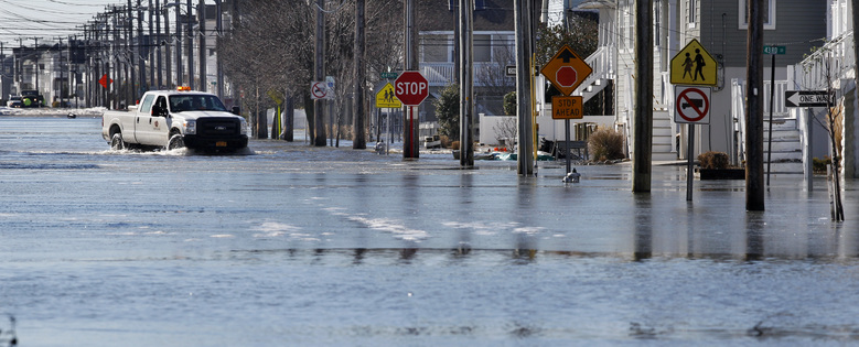 A official drives through flooded streets Sunday, Jan. 24, 2016, in Sea Isle City, N.J. Residents in southern New Jersey's coastal towns continue to deal with flooding caused by the weekend's major snowstorm. Republican Gov. Chris Christie said minor to moderate flooding had occurred during Sunday morning's high tides, mostly in Atlantic and Cape May counties. (AP Photo/Mel Evans)