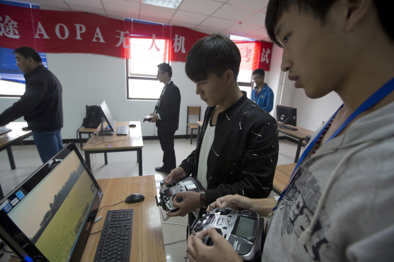 In this Oct. 17, 2015 photo, students learn to operate drones at a school run by TT Aviation Technology in Beijing. TT Aviation Technology Co. – and their instructors – are part of a new cottage industry sprouting up in China, where drones are being deployed in rising numbers and touted as a game-changer in agriculture, logistics, film production and law enforcement. (AP Photo/Ng Han Guan)