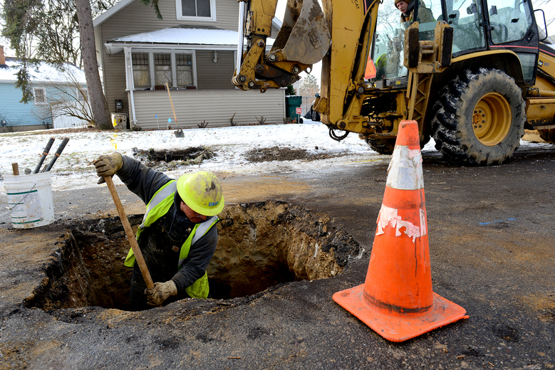 Richard Garza, a BWL mechanic, moves dirt around the water main after replacing the lead water pipe with a new copper one, Friday, Jan. 22, 2016 at a home on Greencroft in Lansing, Mich. Lansing's municipal utility says it's nearly eliminated lead water service lines since concerns in 2004 prompted it to launch a massive program to replace them with copper lines by 2017. (Dave Wasinger/Lansing State Journal via AP)  NO SALES; MANDATORY CREDIT