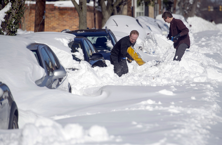 People dig out their cars in Alexandria, Va., Sunday, Jan. 24, 2016. Millions of Americans were preparing to dig themselves out Sunday after a mammoth blizzard with hurricane-force winds and record-setting snowfall brought much of the East Coast to an icy standstill. (AP Photo/Cliff Owen)