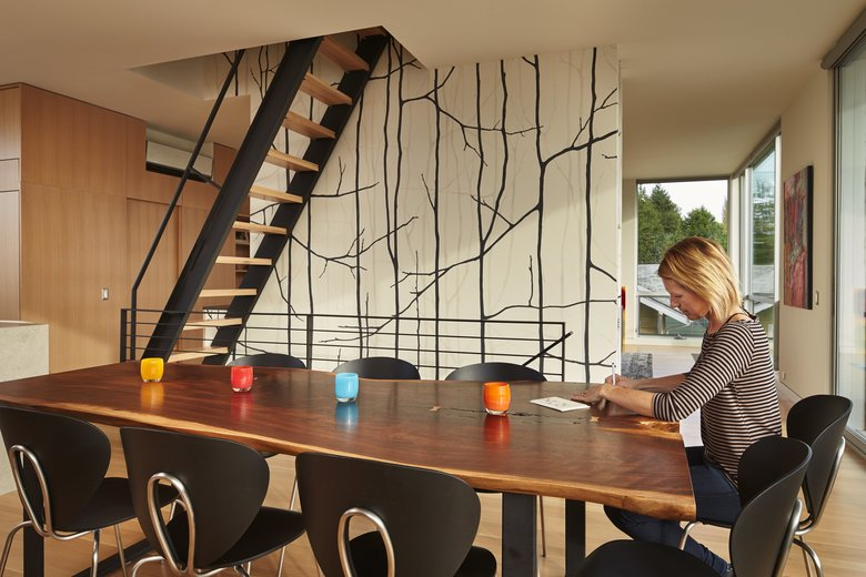 Erika Eckert sits at the custom natural-edge, solid-walnut table slab by , finished by , with a blackened steel frame by Modern Metal Works. The stainless-steel black Globus chairs are from . (Benjamin Benschneider/The Seattle Times)