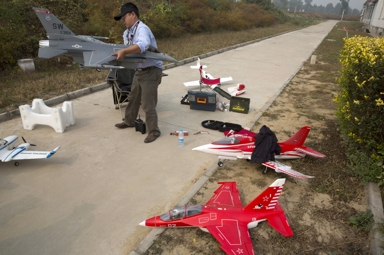 In this Oct. 17, 2015 photo, a drone-flying aficionado prepares his model aircrafts for flight on the outskirts of Beijing. Even as drones offer law enforcement sharply expanded capabilities, authorities in China, as in many other countries, are scrambling to regulate their use. The country is now beginning to set nationwide regulations, which are applauded by many in the Chinese industry. (AP Photo/Ng Han Guan)
